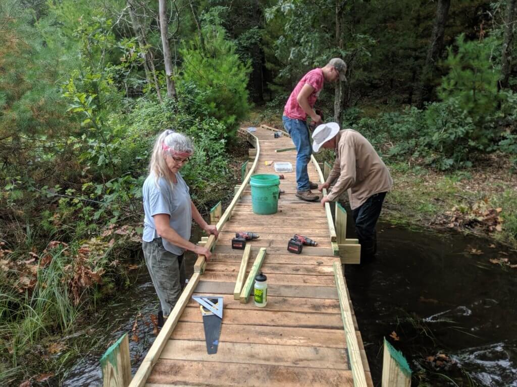 Group repairing a walkway over a creek