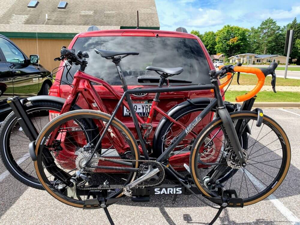 Two bikes on a car rack on the back of an SUV.