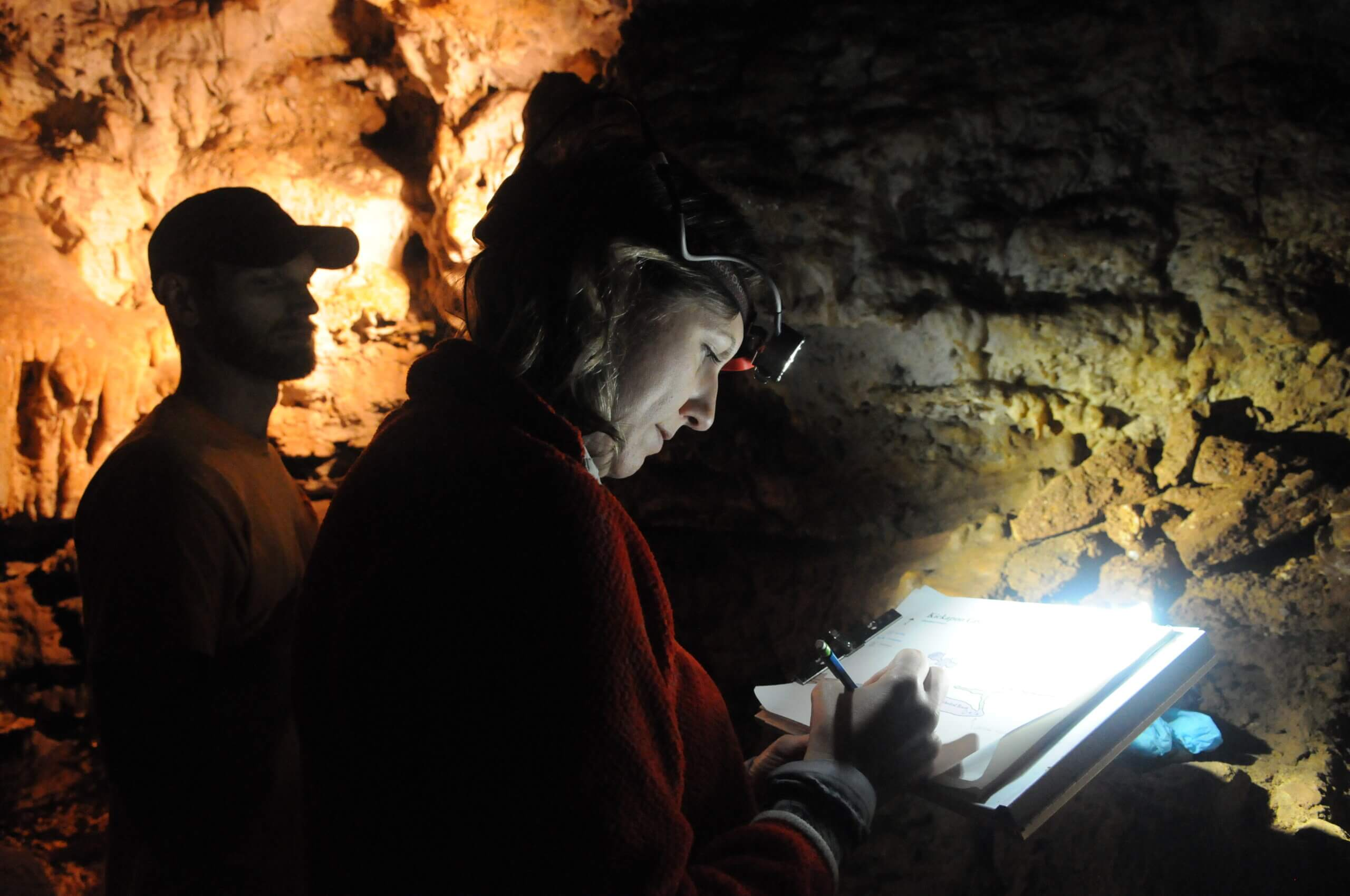Two people explore the Kickapoo Caverns