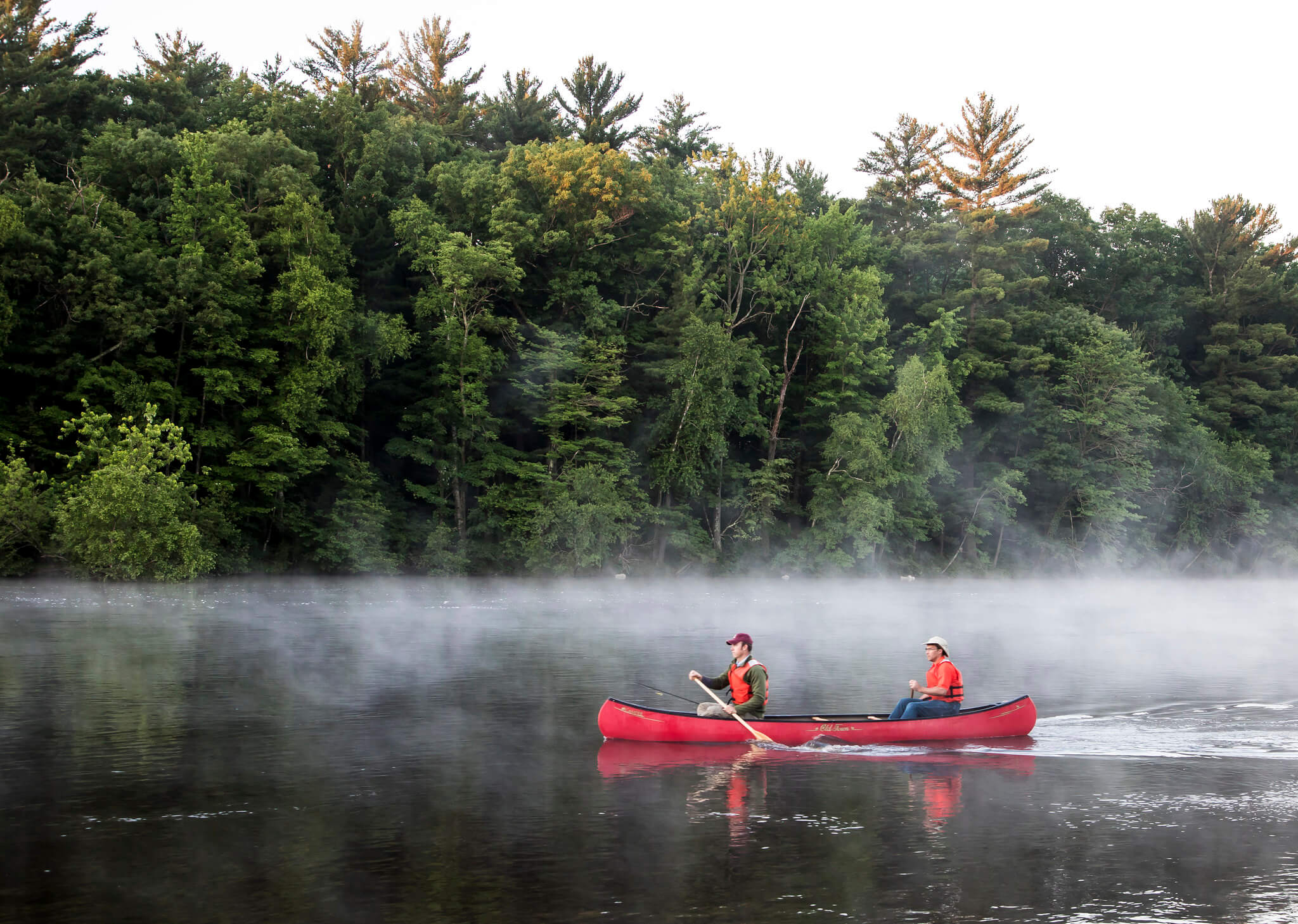Two people paddling in a red canoe on the misty Wisconsin River, with a background of pine trees. The Wisconsin River has benefitted from the Knowles-Nelson Stewardship Program.