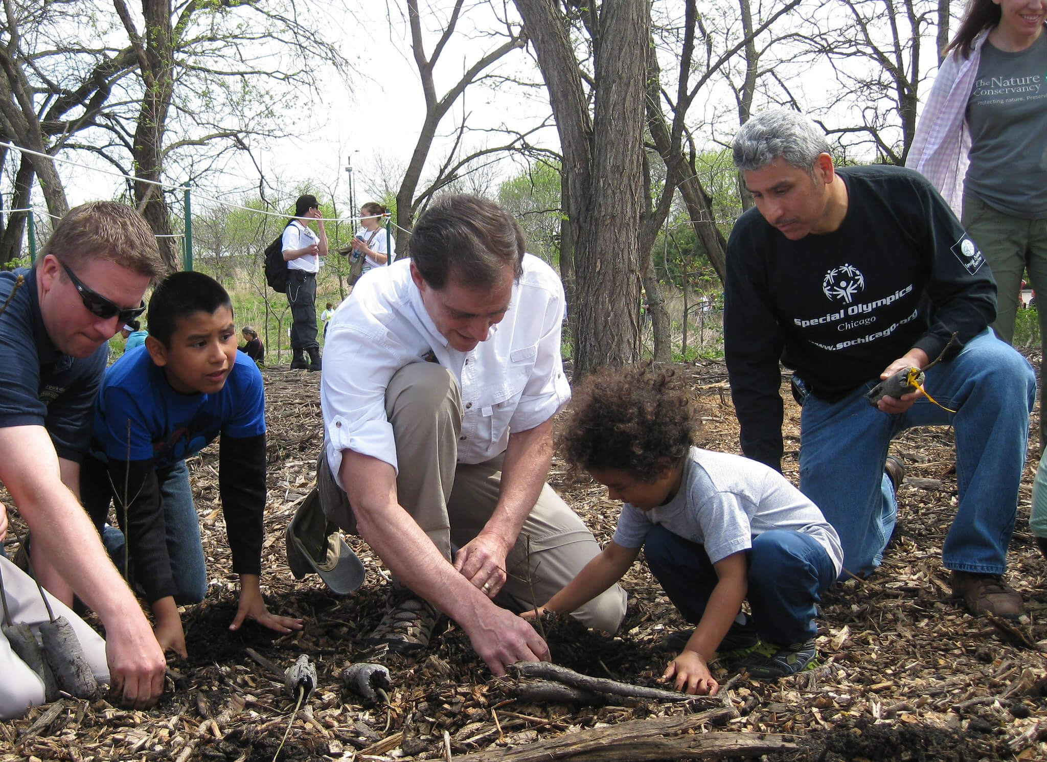 Adults helping kids plant trees. Governor Evers has pledged that Wisconsin will plant millions of trees to fight climate change, and preserve existing forests using the Knowles-Nelson Stewardship Program.