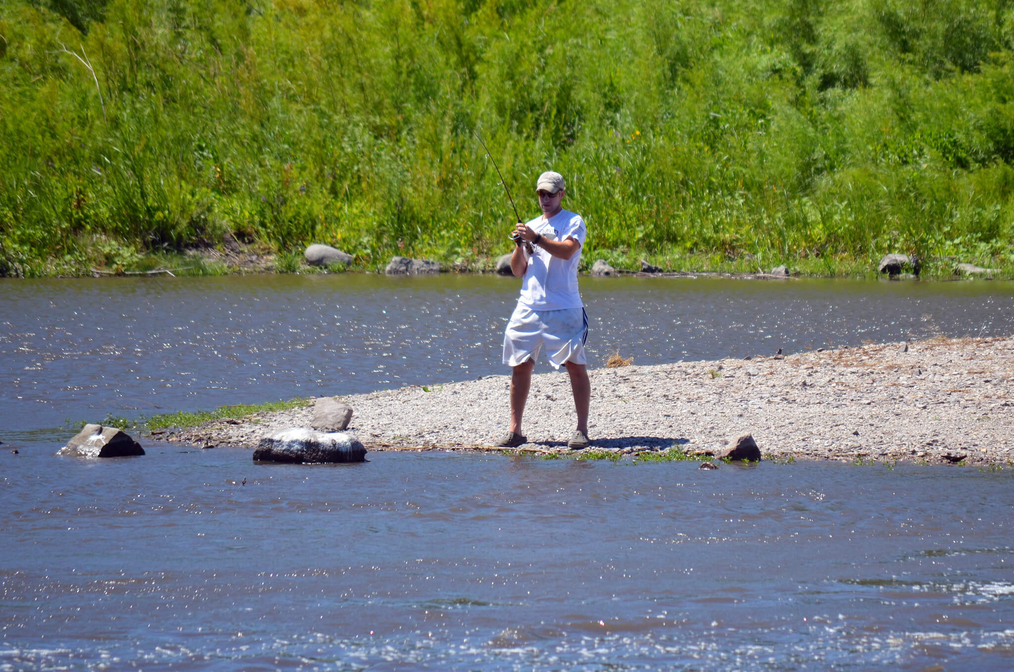 An angler on a lake shoreline. Many similar recreation areas have been protected through the Knowles-Nelson Stewardship Program.